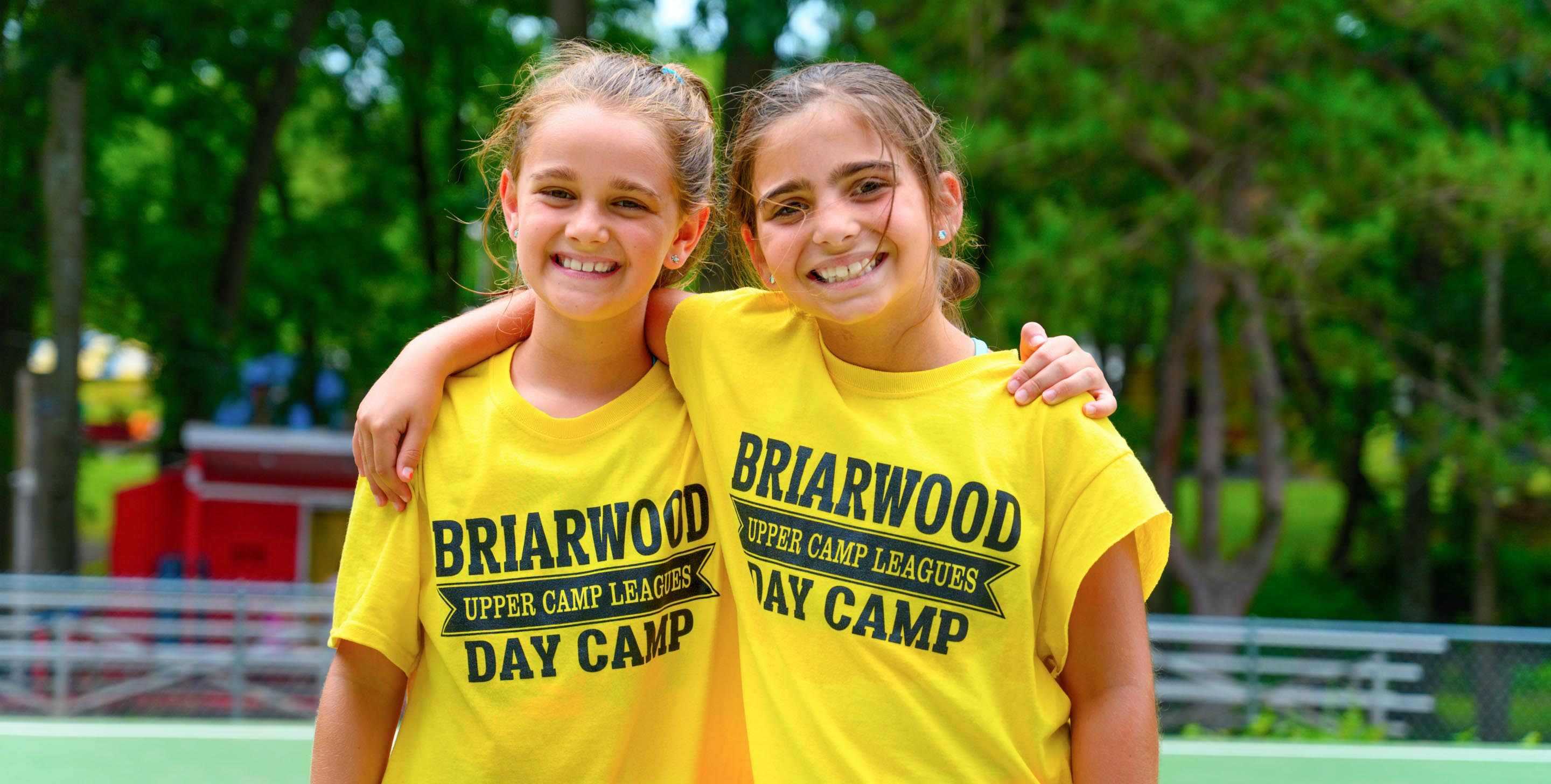 Two girls wearing camp shirts and smiling