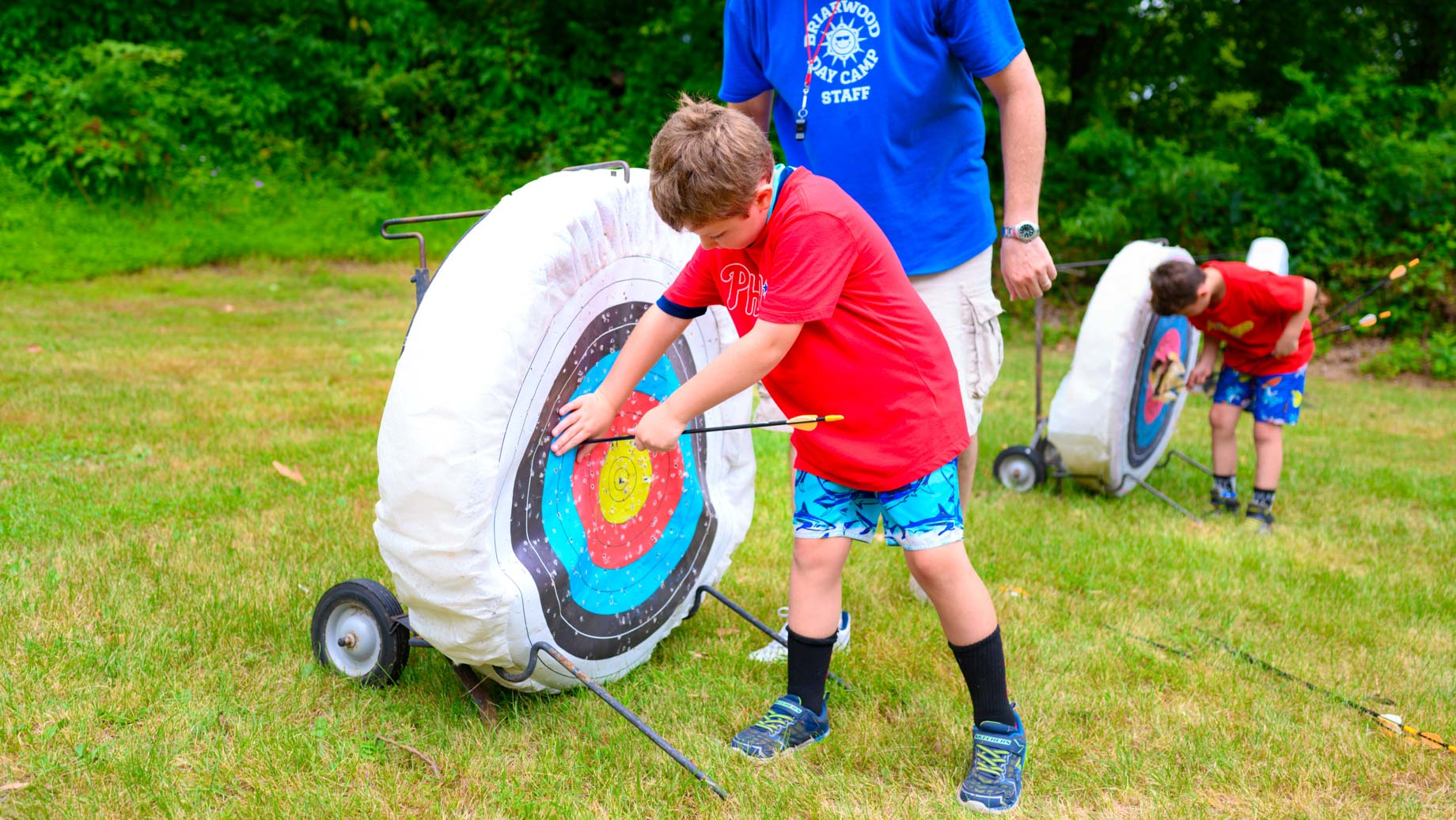 Camper taking archery arrow out of target