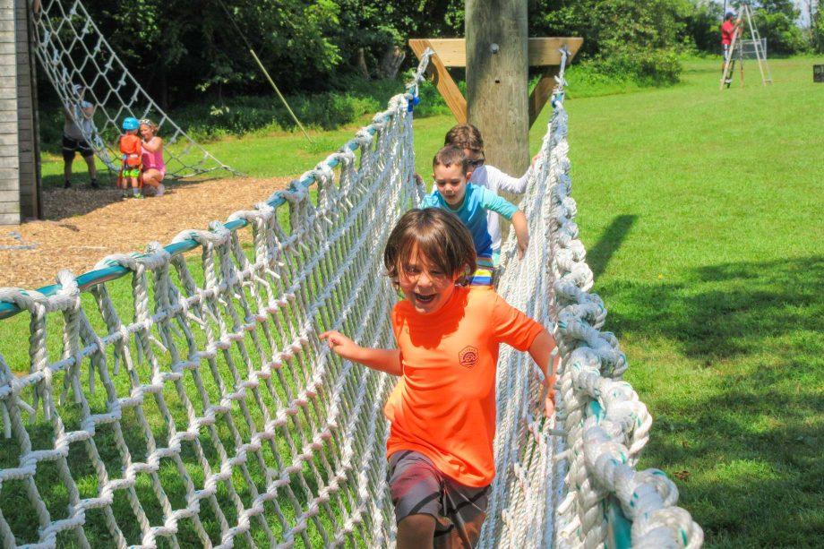 Kids crossing netting for outdoor adventure activity