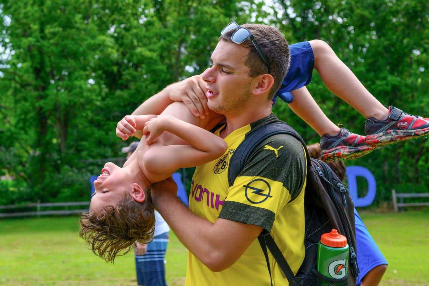Senior staff lifting camper in air