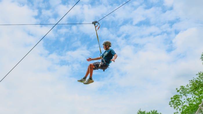 Male camper zip lining for outdoor adventure
