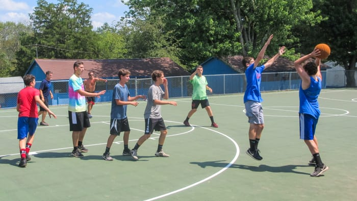 School group playing basketball