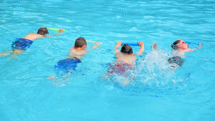Boys learning to swim in pool