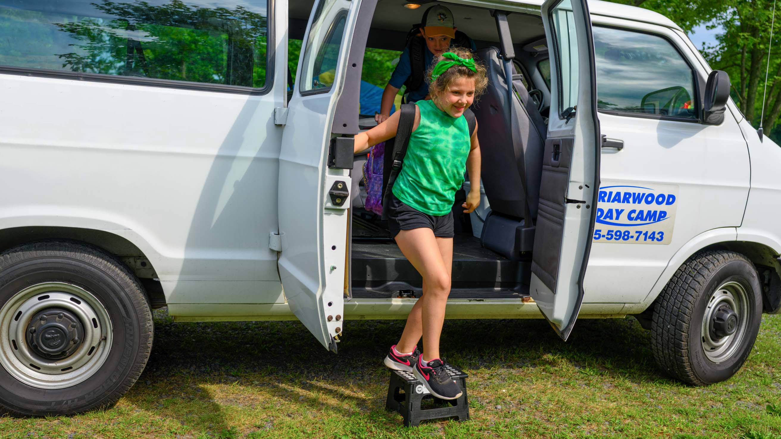 Girl getting out of camp van